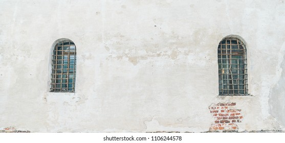 An ancient barred window on a white wall
