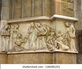 Ancient bas-reliefs on the Windows and walls of historical buildings. Architectural design elements from the past. Biblical parable Jesus fed three loaves of bread. Barselona
