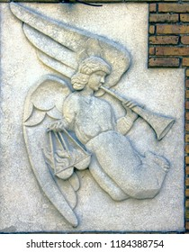 Ancient bas-reliefs on the Windows and walls of historical buildings. Architectural design elements from the past. The angel of judgment with a pipe and scales. Barselona