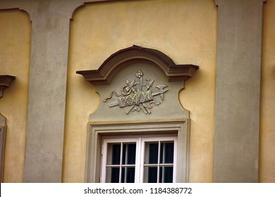 Ancient bas-reliefs on the Windows and walls of historical buildings. Architectural design elements from the past. Warsawa. Ax, poleaxe on the crown of the window