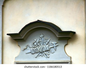 Ancient bas-reliefs on the Windows and walls of historical buildings. Architectural design elements from the past. Warsawa. Shield, ax and spear on the crown of the window