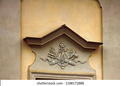 Ancient bas-reliefs on the Windows and walls of historical buildings. Architectural design elements from the past. Warsawa. Quiver and a sword on the crown of the window
