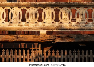 Ancient, beautiful texture, stucco buddha image in stucco circle on balcony and old textured teak wooden backgrounds. Buddhist temple at Lampang, Thailand. Warm tone. The temple is open to the Public.