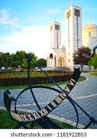 Ancient, Black, Public, Metal SUNDIAL with Roman Numerals, and with Big White Church in background (Nis, Serbia)