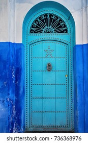 Ancient blue door with knocker and decorative star.