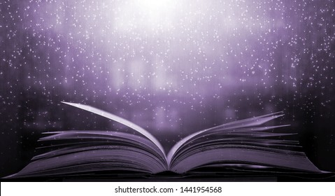 An ancient book that opens with magic, the magic light in the darkness on the wooden table, by the bright light shining down as the power to search for knowledge, religion and background