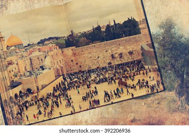 Ancient Book. Western Wall (Wailing Wall or Kotel) in Old city of Jerusalem.  Ancient Holy Land landscape with Old Olive Tree background. Conceptual Image in Vintage Style. Textured old paper