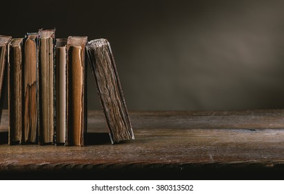 Ancient books on a ruined old table still life, literacy and wisdom concept