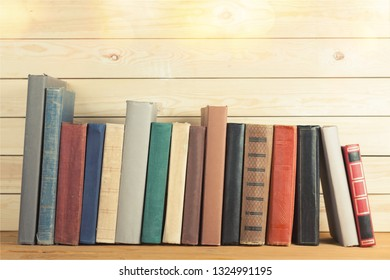Ancient books in a row on wooden background