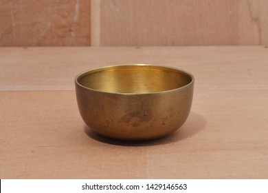 Ancient brass bowl for special ceremony on wooden table. alloy bowl rubbed with stone ,handmade product of thailand