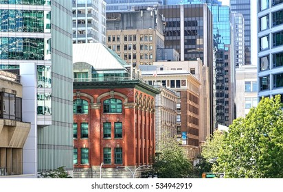 An ancient brick building between modern skyscrapers in downtown Vancouver