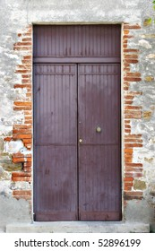 An ancient brick wall with a purple door on a street in Italy.