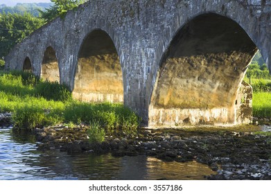 Ancient bridge in Ireland bathed in the sunset light.