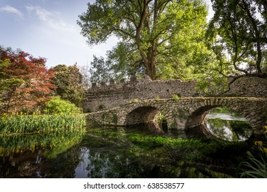 Ancient bridge on the crystalline water in the Garden of Ninfa in the province of Latina, Italy, Europe.