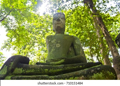 Ancient , broken Buddha statue in the green wild at Wat Umong, Chiangmai, Thailand