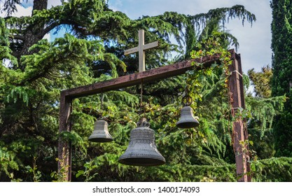 Ancient bronze bells with cross at garden of monastery in Tbilisi, Georgia.