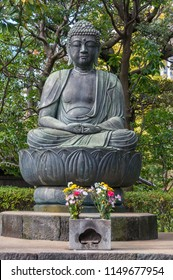 Ancient bronze Buddha statue sitting on lotus in Japanese temple.
