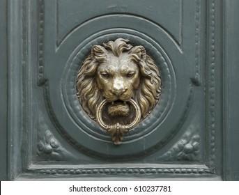 Ancient bronze door knocker handle in the form of a lion's head on a wooden door