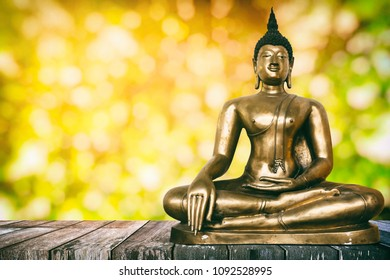 Ancient Buddha Image on Wooden Table with Bokeh Background, Using Buddhist Religion Concept.