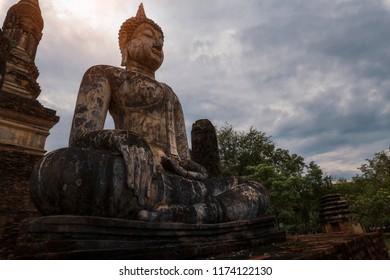 Ancient Buddha sculptures with lens flare in Sukhothai era, Thailand