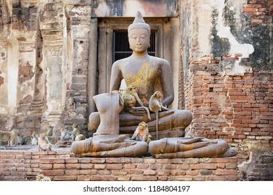 Ancient Buddha statue at he ruins of Prang Sam Yot, originally a Hindu shrine, converted to a Buddhist one in Lopburi, Thailand.