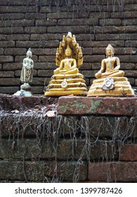 The ancient Buddha statue on the old brick wall at the northern Thai temple.