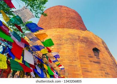 Ancient buddhist Dhamek Stupa (Dharmarajika Stupa) and waving prayer flags. Sarnath, Uttar Pradesh, India