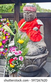 An ancient Buddhist stone sculpture of a priest holding a baby, near fresh flowers, sits in meditation at the entrance to a Buddhist temple in Japan.