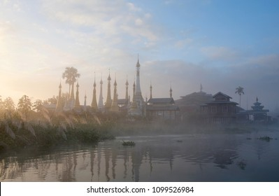 Ancient buddhist stupa and wooden monastery over mist at sunrise on Inle lake, Shan state, Myanmar