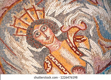 Ancient byzantine natural stone tile mosaics with face of mythical goddess and floral ornament, Madaba, Jordan