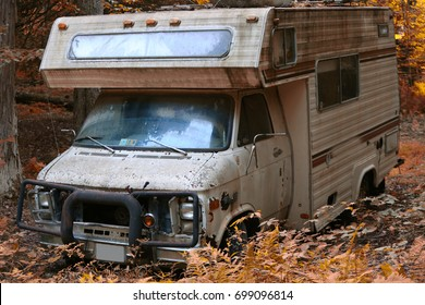Ancient camper abandoned in autumnal foliage in natural light