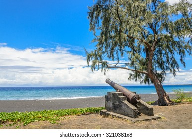 Ancient cannon on a beach under a tree, la Reunion island