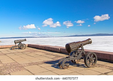 Ancient cannons in Petrozavodsk shore, frozen Onega lake in winter