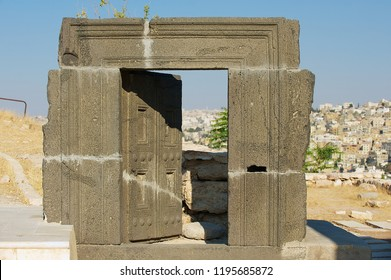 Ancient carved Basalt Door at the Citadel of Amman with the city at the background in Amman, Jordan.