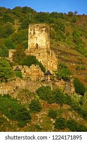 Ancient castle Burg Gutenfels on top of mountain covered with vineyards at Rhine Valley (Rhine Gorge), view from across river, Germany, on a sunny summer evening. Mighty romantic ruins from fairytale.