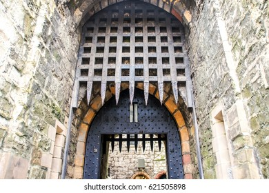 Ancient castle palace in Isle of Man. Castle wall tower and door gate. Castles walls and window isolated. Castles palace fort landscape background. Stone architecture Giant metal door gate