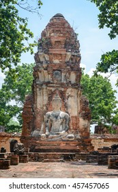 Ancient cement buddha statue in front of ruined pagoda at ancient temple in world heritage city of Ayutthaya, Thailand