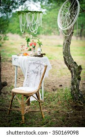 Ancient chair against wedding decoration in style of a shabby chic. Decoration of a wedding photoshoot.  Details of a wedding decor.
