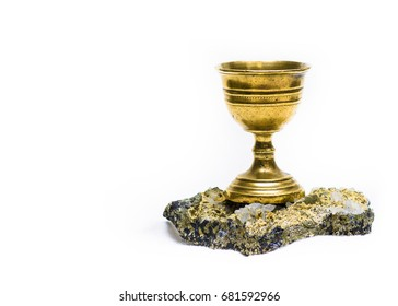 Ancient chalice of copper on quartz stone on white background.