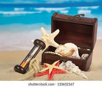 Ancient chest with sea cockleshells, hourglasses and a rope on sand
