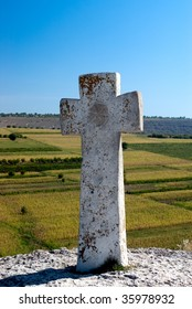 Ancient Christian stone cross on the hill with blurred fields in the background and blue sky, Old Orhei place in Moldova