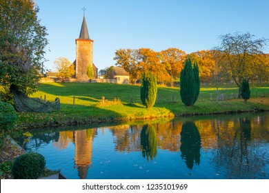 Ancient church on the edge of a pond along trees below a blue sky in sunlight at fall