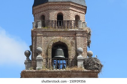Ancient church steeple with stork nests under clear blue sky.