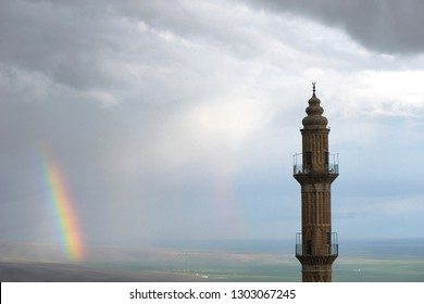 ancient city mardin. cut stone architecture of ancient mosque in Mardin with green crop background. rainbow in the mountains, ancient city mardin