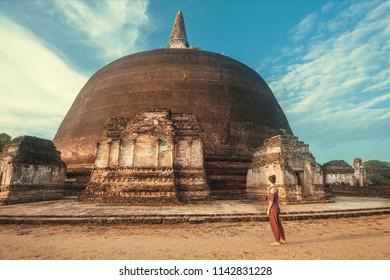 Ancient city Polonnaruwa and woman walking past sacred stupa Rankoth Vehera. Buddhist structure of 12th century, Sri Lanka. UNESCO World heritage Site.