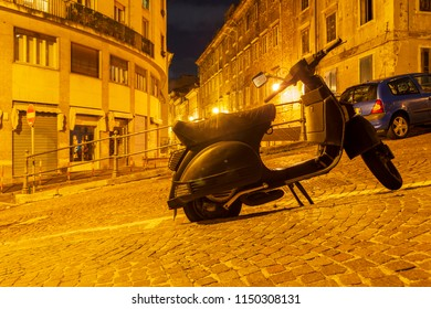 ancient city street with scooter parked on pavement in Trieste, Italy