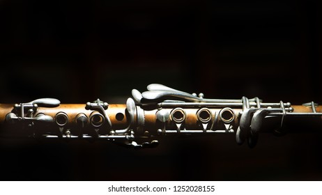 Ancient clarinet. Detail on a black background.