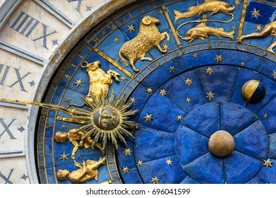 Ancient clock Torre dell'Orologio on St Mark's Square, Venice, Italy. It is one of the main travel attractions of Venice. Detail with Zodiac signs and sun close-up. Concept of astrology and time.