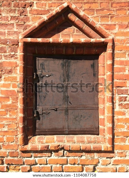 Ancient closed church window. Old metall shabby shutter in stone frame. Vintage architectural object on orange brick wall. Hinge on dark brown rough metallic surface.