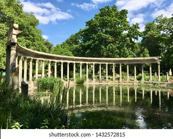 The ancient columns of Parc Monceau are reflected in the water of the oval basin, in the sun, in summer. This public garden is located in the 8th arrondissement of Paris